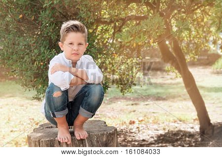 Boy 8 years old sitting on a tree stump on a sunny summer day. Kid outdoor enjoying nature. Handsome Boy barefoot sitting looking stright.