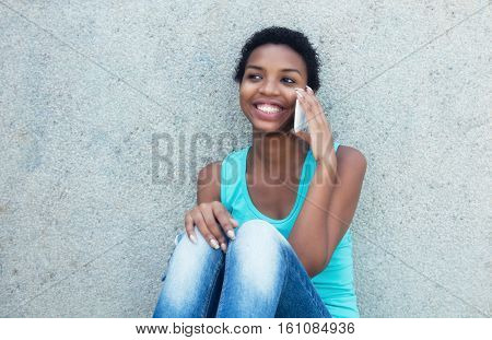 Happy african girl with cell phone outdoor in the summer
