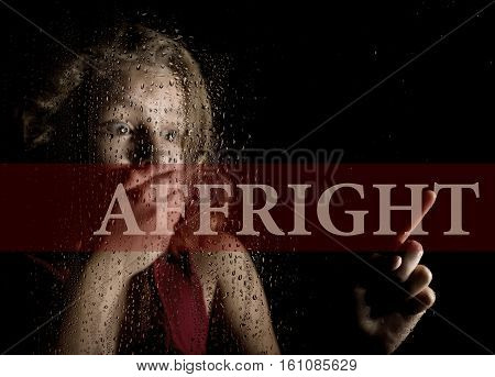 affright written on virtual screen. hand of frightened young girl melancholy and sad at the window in the rain