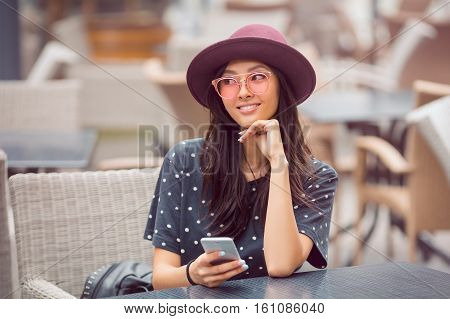 Cafe city lifestyle woman on phone texting text message on smartphone app sitting outdoor in trendy urban cafe. Cool young modern mixed race Asian Caucasian female model in fashion retro look style