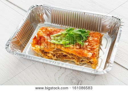 Healthy eating concept. Lunch foil box, take away organic food. Weight loss diet. Fat free lasagna on white wood, closeup