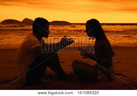 Love couple with relationship difficulties outdoor at beach at sunset