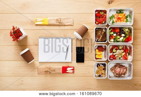 Healthy nutrition plan. Fresh daily meals delivery. Restaurant food for two, vegetable, meat and fruits in foil boxes, coffee, tablet and mobile. Top view, flat lay on wood with copy space