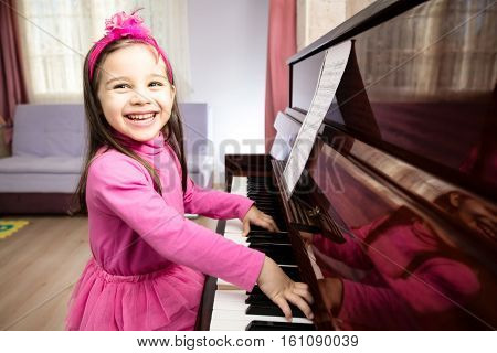Little girl is reading notes and practicing piano
