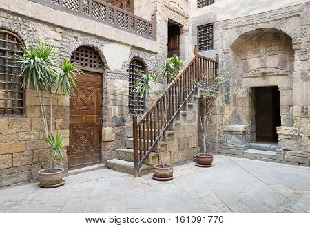 cairo, Egypt - December 10, 2016: View of the courtyard of Beit El Set Waseela (Waseela Hanem House), showing a wooden closed door and two windows with interleaved wooden grid and stair with wooden handrail leading to the upper floor, Medieval Cairo