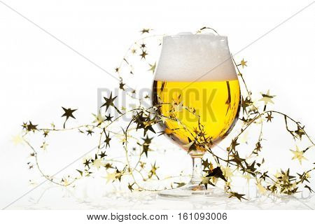 Full snifter glass of pale lager of pilsner beer with a large head of foam and golden christmas tinsel on white background