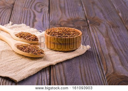 Brown flax seeds or flax seed in a small bowl on sacking and two wooden false on a brown wooden table