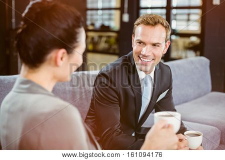 Businessman and businesswoman having a discussion during breaktime in office