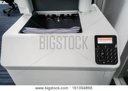 close up printer output tray with paper sheet