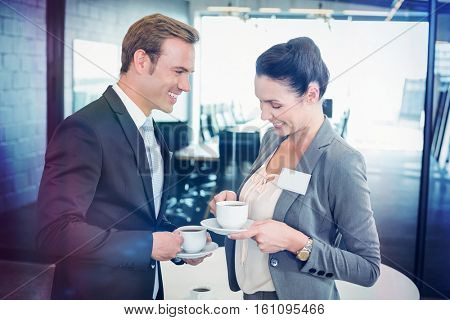 Businessman and businesswoman having tea during breaktime in office