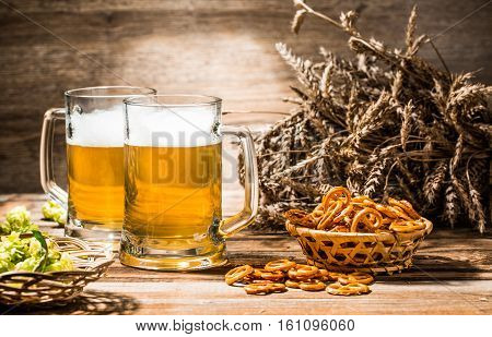 Two mugs of foam beer stand on wooden table with pretzels, wheat and hops