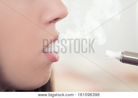 woman smoking electronic cigarette and enjoying smoke.Closeup detail of female with electronic cigarette horizontal shot. Girl smokes and exhaling flavored steam. Concept: safe way of smoking how to stop smoking