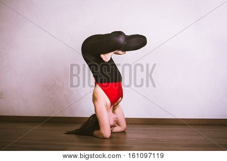 Young pretty woman in black leotard practicing yoga