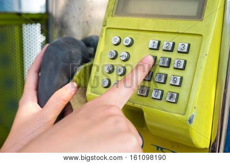 Woman hand dialing a payphone, communication concept
