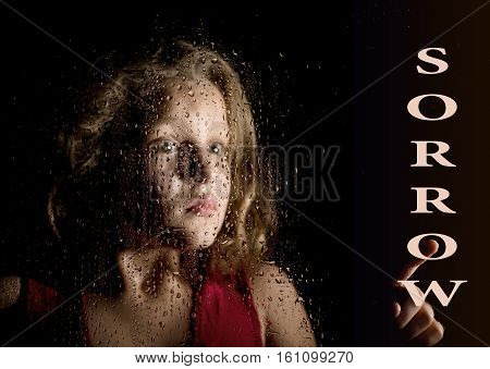 sorrow written on virtual screen. hand of frightened young girl melancholy and sad at the window in the rain