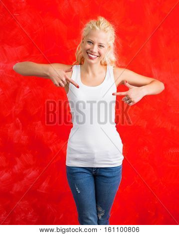 Woman in white tank top on red background pointing at it with both hands