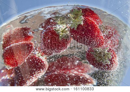 red ripe strwberries in crystal clear fresh water with sunlight