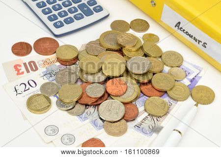 A financial still life with an accounts folder calculator coins notes and pen