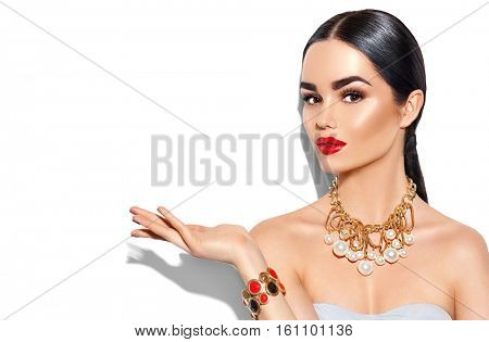 Beauty fashion model brunette girl portrait. Sexy young woman with perfect makeup and trendy golden accessories showing empty copy space on the open hand palm for text, fashion glamour female.