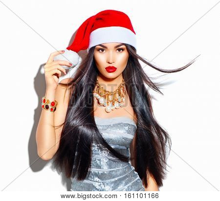 Beauty Christmas fashion model girl with long straight flying hair in red santa hat, beautiful make up, Sexy brunette young woman portrait. Stylish female, fashionable party clothes and accessories