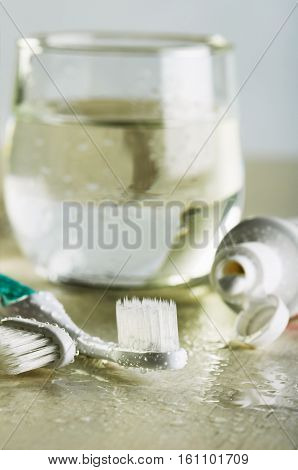 Two Toothbrushes, Toothpaste And A Glass Of Water On A Wet Table Close-up Vertical