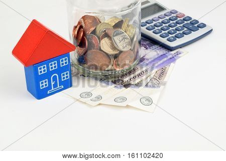 A jar of Sterling coins house and calculator to represent Sterling home finance.