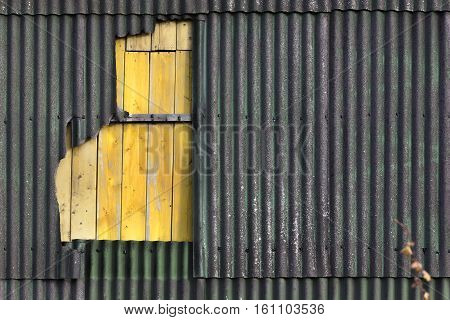 Old damaged wall of corrugated asbestos material repaired with yellow timber