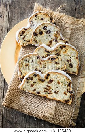 Slices of Christmas stollen. Traditional German Christmas dessert on wooden background. Top view