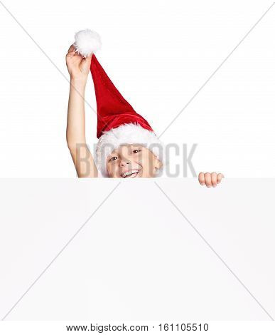 Smiling little boy wearing Santa Claus hat, holding white board. happy child peeking over edge of blank empty paper with copy space.