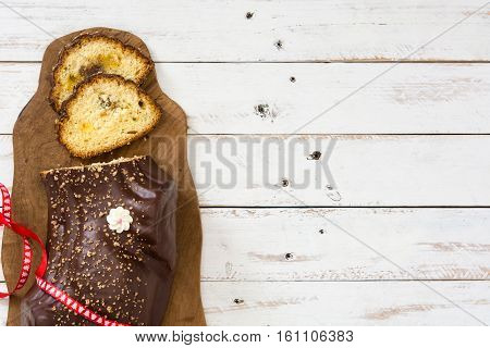 Chocolate yule log christmas cake and christmas ornament on white wooden background