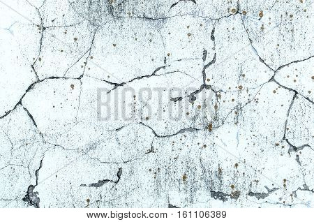Texture of whitewashed concrete wall with sharp cracks and spots of lichen close up