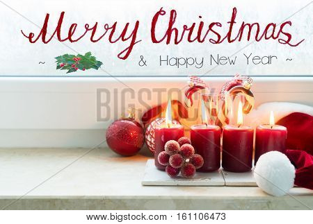 Christmas scene with four red burning candles on windowsill with copy space and merry christmas greetings