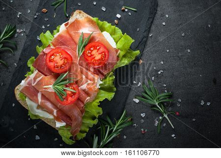 Ciabatta sandwich with  salad leaves jamon serrano and mozzarella cheese over stone background. Top view with copy space. Mediterranean Food background.