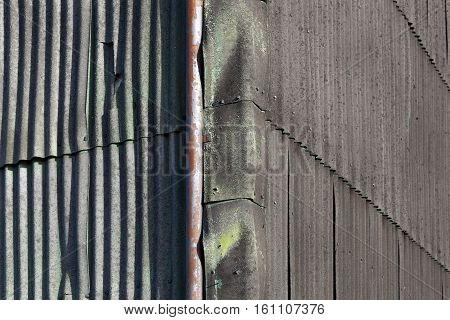 Old walls of corrugated asbestos material and a rusty drainpipe