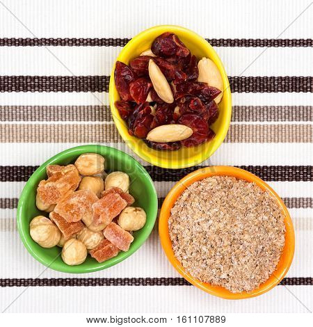Healthy and weight loss diet products. Cups with wheat bran, mixtures of nuts, dried fruits and berries. Hazelnut, almond, papaya, cranberries