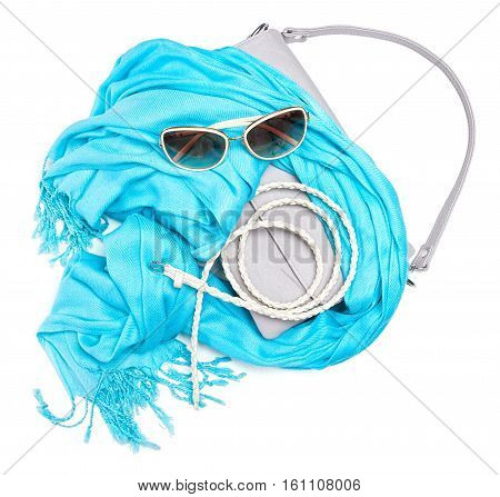 Set of beautiful fashion accessories for women. Small gray handbag with short strap, blue fringe scarf, skinny braided belt and sunglasses on white background
