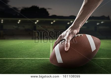 Cropped image of sports player holding ball against rugby pitch 3D