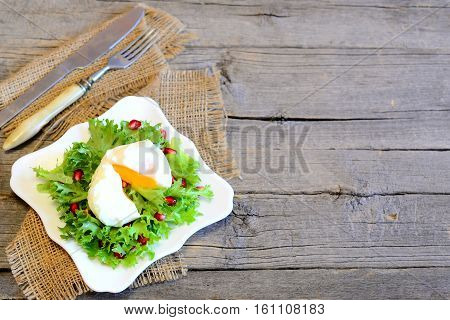 Poached egg, fresh lettuce leaves with pomegranate seeds and olive oil. Tasty salad on a plate on wooden background with copy space for text. Diet food. Top view