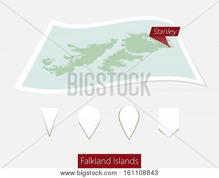 Curved Paper Map Of Falkland Islands With Capital Stanley On Gray Background. Four Different Map Pin