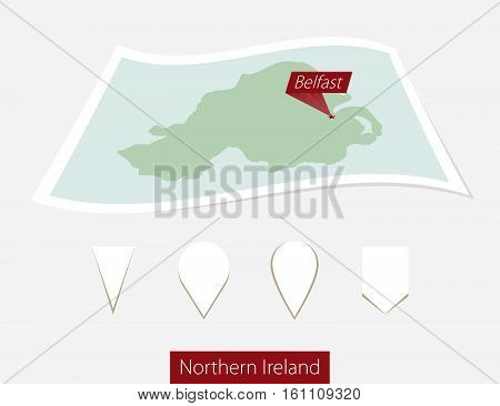 Curved Paper Map Of Northern Ireland With Capital Belfast On Gray Background. Four Different Map Pin