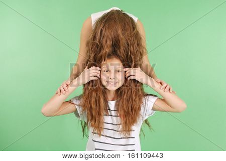 Funny portrait of two young girls with long hair isolated on green