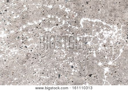Texture of stained gray concrete with spots of white paint close up