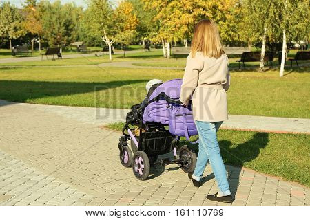 Woman with baby stroller walking in green park