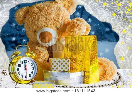 Teddy bear gifts and an alarm clock on Christmas night on a background of icy window and snowy garden
