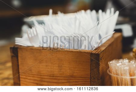 Set of plastic disposable cutlery, forks and knives and individual packed toothpicks in wooden box. Catering utencils for bistro fast food cafe on country fair, detail closeup
