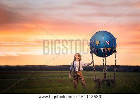 Little boy with aerostat in the field
