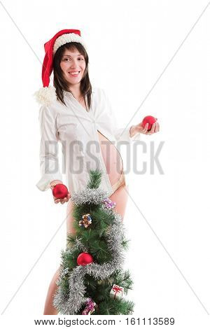 Pregnant young woman near decorated christmas tree isolated on white
