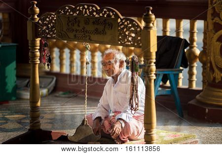 Mandalay, Myanmar-13 December 2015. Man ringing burmese gong the triangular-shaped Kyeezee or 'spinning' gong for the time of meditation at Kuthodaw temple on 13 December, 2015 in Mandalay, Myanmar.