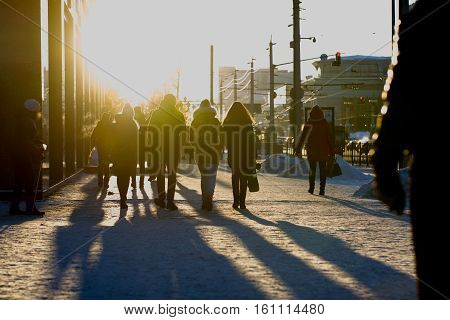 Crowded street at winter cold sunsed, blurred background, telephoto