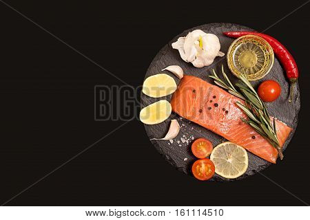 Fillet Of Salmon, Tomato And Herbs Over On Black Stone Slate.